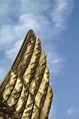 Golden wing with blue sky — Stockfoto