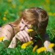 Stock Photo: Young pretty woman in wreath of dandelions in the meadow solar day