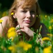 Young pretty woman in wreath of dandelions in the meadow solar day — Stock Photo