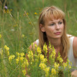 Woman sitting among yellow flowers — Stock Photo