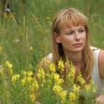 Woman sitting among yellow flowers — Stock Photo
