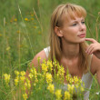 Woman sitting among yellow flowers — Stock Photo #6641407