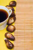 Chocolate sweetmeats in form seashell and cup of coffee — Stock Photo