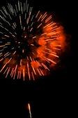 Uno scoppio di fuochi d'artificio rosso-arancio contro un cielo di notte. — Foto Stock