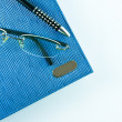 Glasses on blue notebook with black pen in isolation — Stock Photo