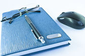 Glasses and black pen on blue notebook with mouse in isolation — Stock Photo