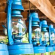 Perspective view of storm lanterns hanged on wooden counterpoise — Stock Photo