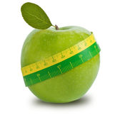 Green apple with measuring tape — Stock Photo