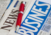 Red pen on the business newspaper — Stock Photo