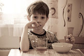 The boy has breakfast — Stock Photo
