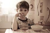 The boy has breakfast — Stock Photo