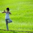 Girl practicing yoga,standing in paddy field — Stockfoto