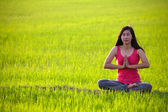 Girl practicing yoga,sitting in paddy field — Stock Photo