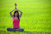 Girl practicing yoga,sitting with lotus flower in paddy field — Stock Photo