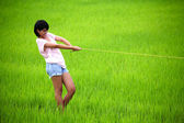 Beutiful young girl pulling yellow rope in paddy field — Stock Photo