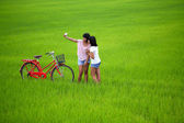 Two girls taking a photo with bike in paddy field — Stock Photo