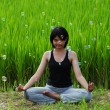 Girl practicing yoga in paddy field — Stok fotoğraf #6381694