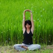 Girl practicing yoga in paddy field — ストック写真