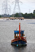 Wooden fishing boat and electrical tower in industrial area — Stock Photo