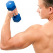 Young man lifting blue dumbbells weights by hand — Stock Photo