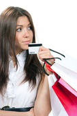 Woman standing, holding credit card and shopping bags in hand — Stock Photo