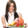 Woman holding a plate with turkey ham — Stock Photo
