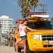 Lifeguard woman on the ocean sand beach near save lifeguard car — Stock Photo