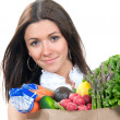 Woman holding a shopping bag full of vegetarian groceries — Stock Photo