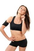 Fitness beautiful slim brunette sport woman listening to music — Stock Photo