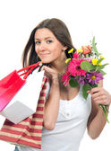 Woman holding shopping bags, presents and bouquet of flowers — Stock Photo