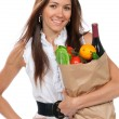 Happy young woman holding a paper shopping bag full of groceries — Stock Photo