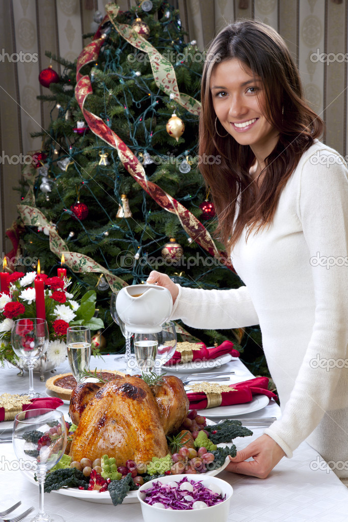 Family christmas dinner celebration. Woman holding Roasted turkey, red candles, fir tree ornament decoration, rich table with meals, champagne glasses, pie, gra — Stock Photo #6696664