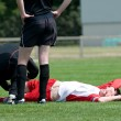 Stock Photo: Soccer injured at football lying on grass
