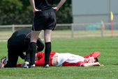 Soccer injured at football lying on the grass — Stock Photo