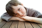 Young boy on a table looking photograph — Stock Photo