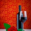 Stock Photo: Bottle of red wine with half filled glass and red rose on pattern backgroun