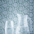 Glass and jug filled with fresh water - Stock Photo