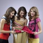 Three beautiful women shopping a dress — Stock Photo