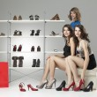 Three young women sitting trying shoes looking happy — Stock Photo #5545227