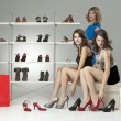 Three young women sitting trying shoes looking happy — Stock Photo