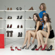 Three young women sitting trying shoes looking happy — Stock Photo #5545231