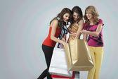 Young women looking happy shopping bags — Stock Photo