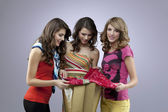 Three beautiful women shopping a dress — Stock Photo