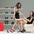 Two young women trying on high heels - Stockfoto