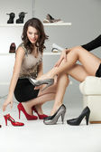 Two young women trying on high heels — Stock Photo