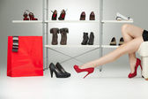 Red high heels on long legs — Stock Photo
