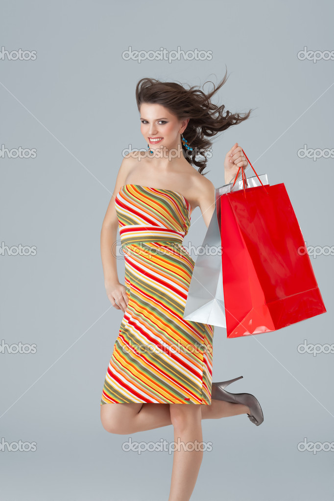 Joyfull brunette carrying shopping bags wind blowing — Stock Photo #5663615
