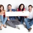 Happy friends showing white banner - Stockfoto