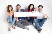 Happy friends showing white banner — Stock Photo