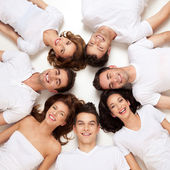 Smiling friends in circle on their back — Stock fotografie